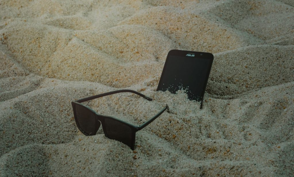 phone and sunglasses in sand