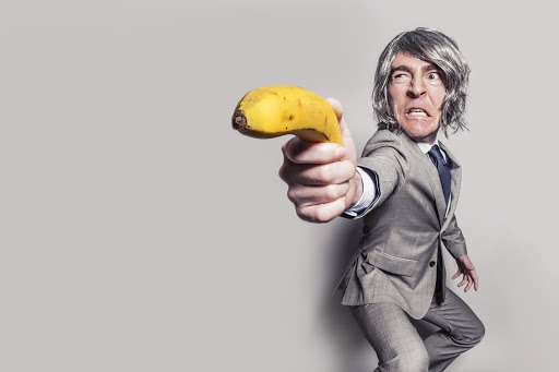 Guy in grey suit holding banana